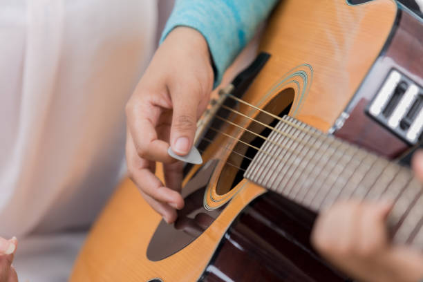 Closeup of guitar body being played with a pick In this closeup, human hands can be seen playing a guitar.  Focus is on the strumming hand holding a pick.  Another hand can be seen  on the fret board chording. folk music stock pictures, royalty-free photos & images