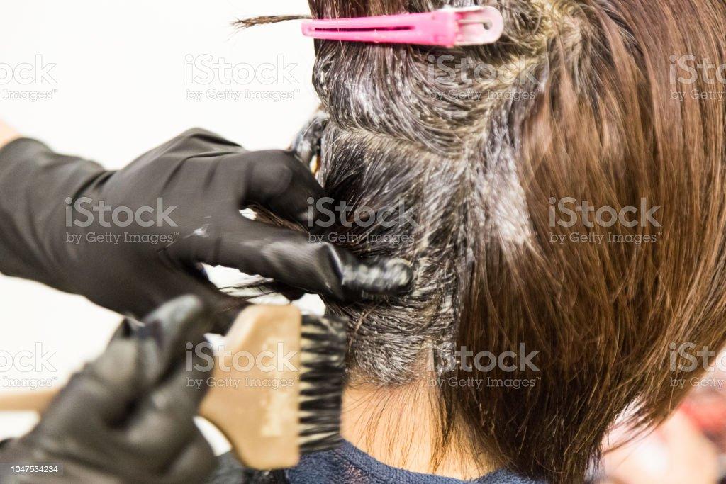 Closeup of hair dresser applying chemical color dye onto hair stock photo