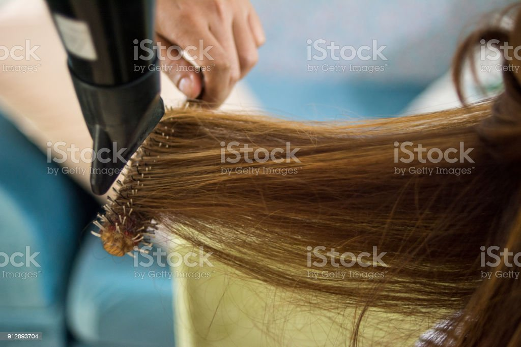 Close-up of hair dryer for hair drying concept hair salon female stylist. Woman getting her hair dried at the hair salon stock photo