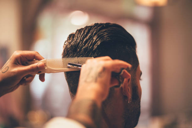Close-up of hairstylist's hands cutting strand of man's hair stock photo