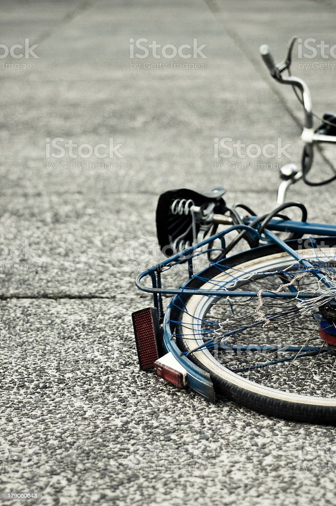 Close-up of half a bicycle laying on asphalt with tire near stock photo