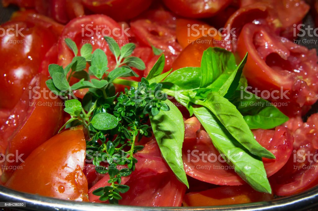 Closeup of halved and seeded Roma tomatoes with basil, oregano and thyme. stock photo