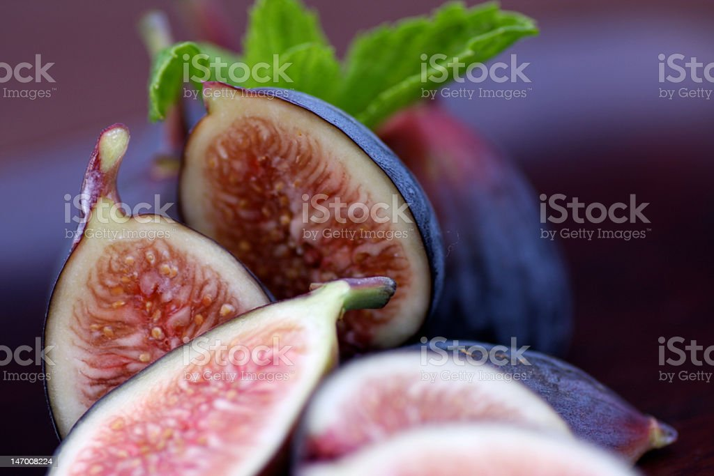 Close-up of halved black figs and leaves stock photo