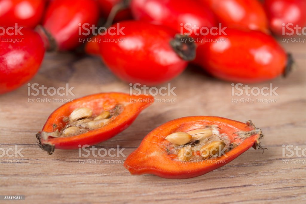 Close-up of halved red rosehip with core on wooden background stock photo