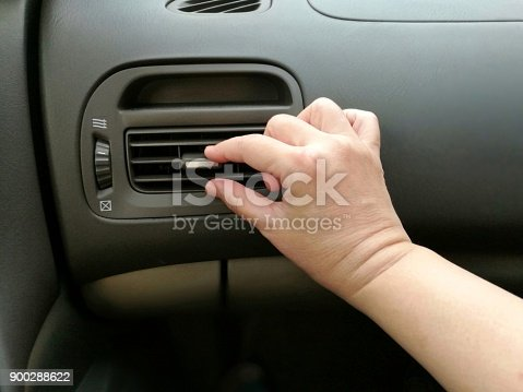 istock Close-up of hand adjusting air vents to change wind direction inside a car. 900288622