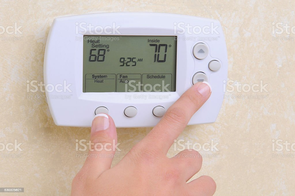 Closeup of Hand and Thermostat stock photo