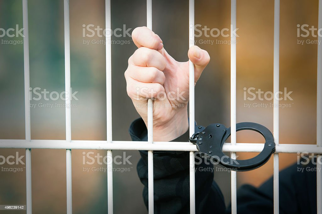 closeup of hand being handcuffed stock photo