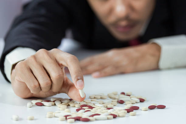 close-up of hand businessperson holding pills in stress from overworked in workspace blurred. concept of failure working - china drug foto e immagini stock