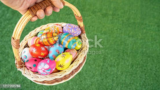 Closeup of hand carrying colorful easter eggs in basket over green grass floor.