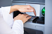 Close-up Of Woman's Hand Entering Pin On ATM Machine Keypad