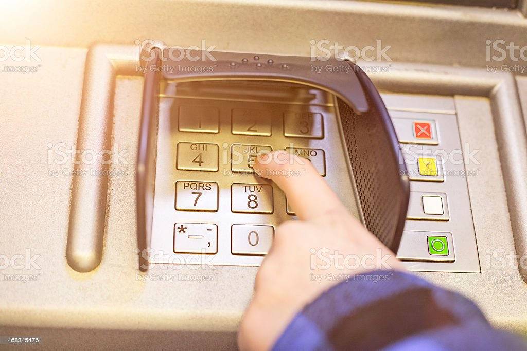 Close-up of hand entering PIN on ATM, bank machine keypad stock photo