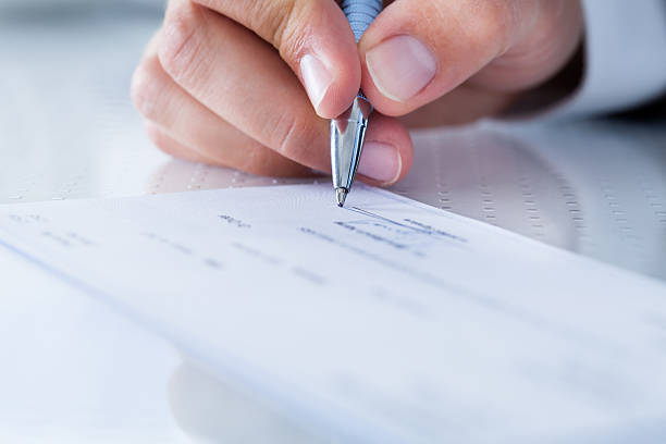 close-up of hand filling cheque - blank check stock photos and pictures