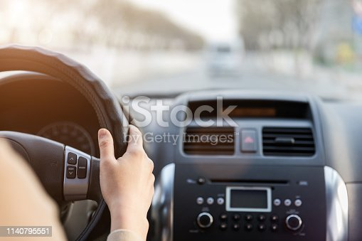 Close-up of hand holding a steering wheel driving