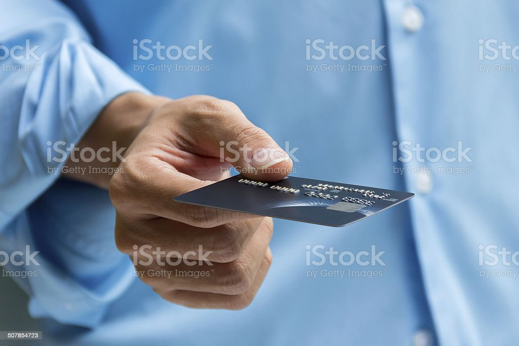 Closeup of hand holding and giving credit card for payment stock photo