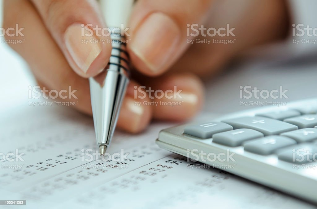 Closeup of hand holding pen against paper with numbers  stock photo