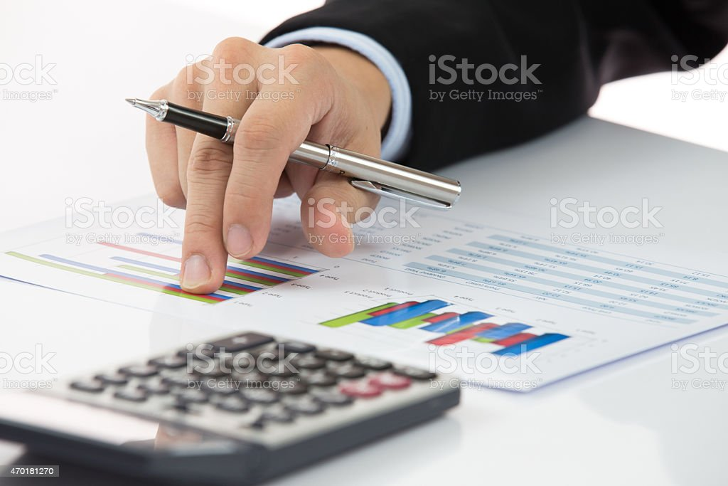Close-up of hand holding pen with chart next to calculator stock photo