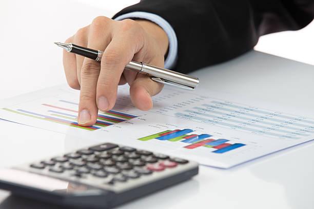 Geschäftsmann Analysieren von Investitionen Diagramme an seinem Arbeitsplatz – Foto
