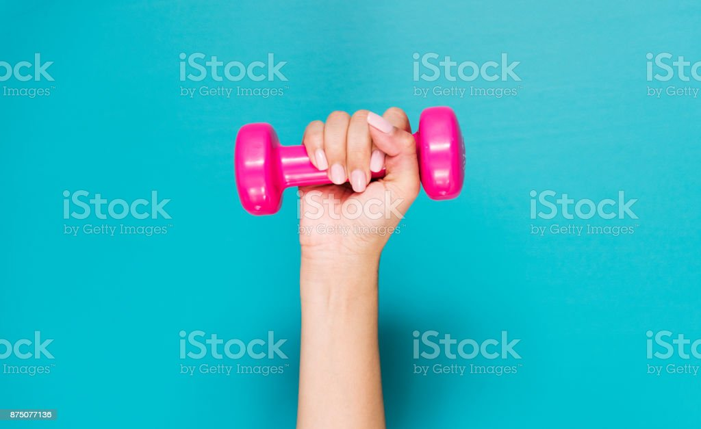 Closeup of hand holding pink dumbbell stock photo