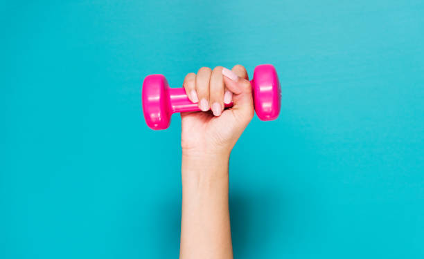 closeup of hand holding pink dumbbell - dumbbell stock pictures, royalty-free photos & images
