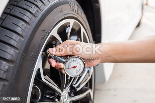istock Close-Up Of Hand holding pressure gauge for car tyre 540718950