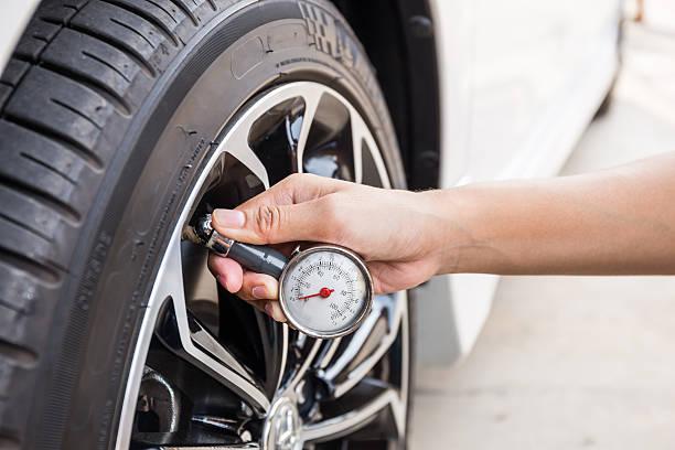 close-up of hand holding pressure gauge for car tyre - autoband stockfoto's en -beelden
