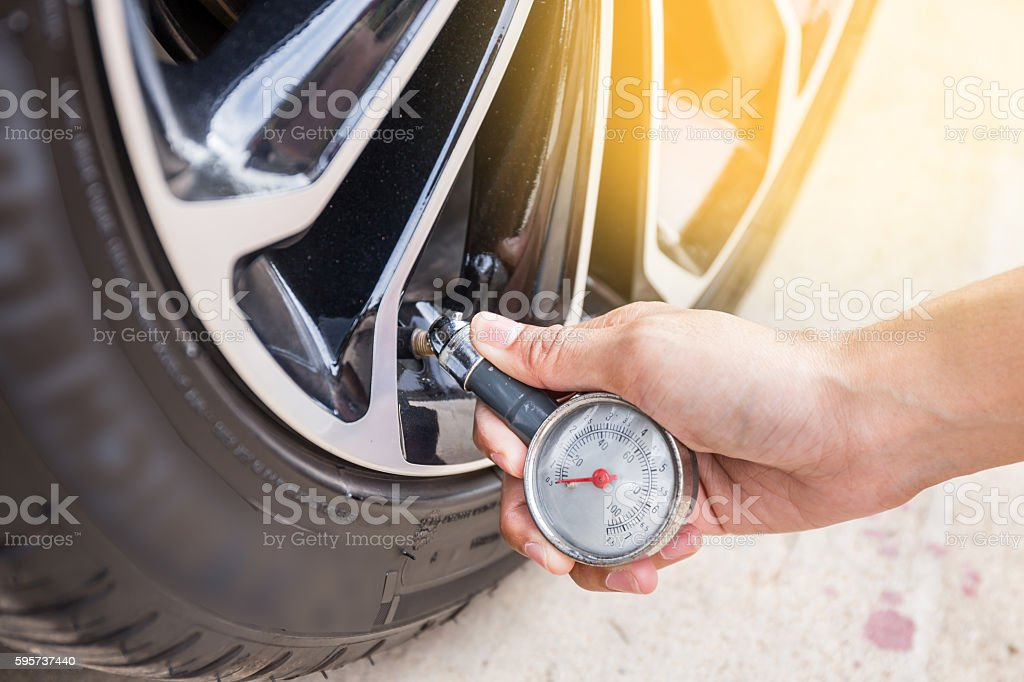 Close-Up Of Hand holding pressure gauge for car tyre pressure stock photo