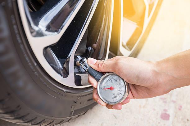 close-up of hand holding pressure gauge for car tyre pressure - pression physique photos et images de collection