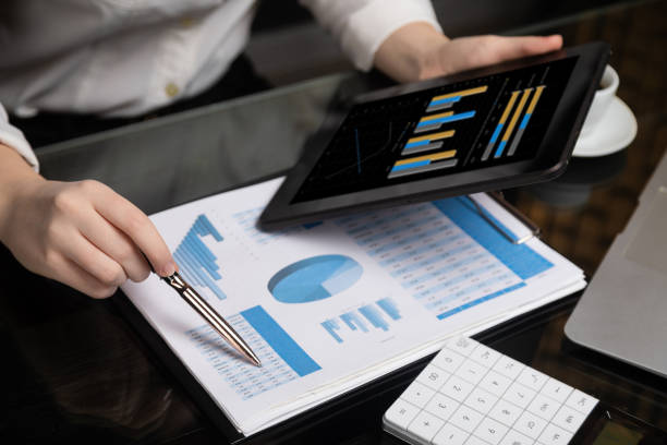 Close-up of hand holding tablet and point pen at chart stock photo
