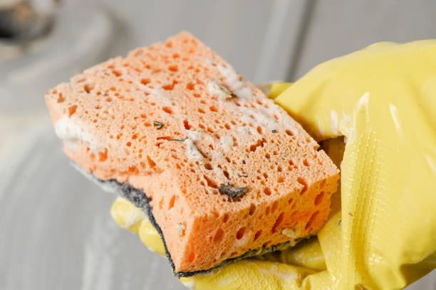 close-up of hand in a yellow glove with sponge. - spugna per le pulizie foto e immagini stock