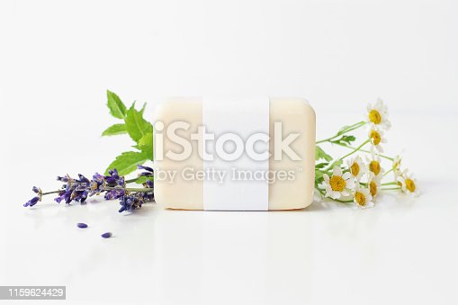 istock Closeup of hand made herbal soap bar in blank paper label package. Mint leaves, lavender and feverfew flowers on white table backround. Spa concept. Skin product mockup scene. Cosmetic product. 1159624429