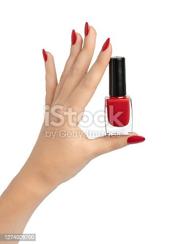 closeup of hand of a young woman with long red manicure on nails against white background. Female hand holding red nail varnish bottle. Female hand red nail design.