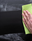 close-up of hand of person cleaning dirty chalkboard with sponge cloth