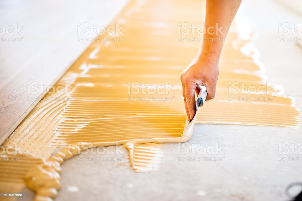 close-up of hand of worker adding glue during parquet installation - foto de stock
