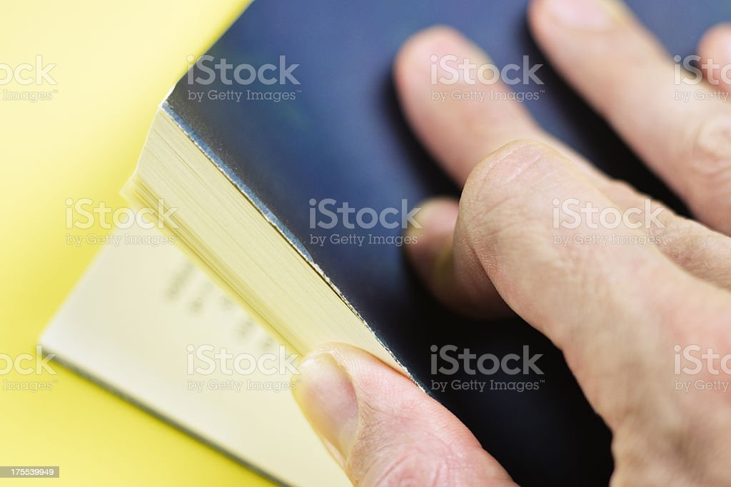 Close-up of hand opening a book from the back royalty-free stock photo