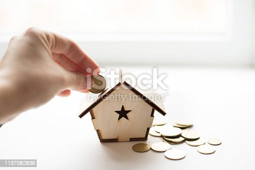 istock Closeup of hand putting coin in wood house piggy bank on white background. place for text. Saving money, home loan, mortgage, a property investment for future concept. 1137082836