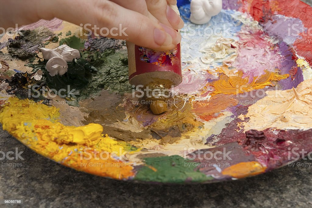 close-up of hand squeezing yellow oilpaint on palette royalty-free stock photo