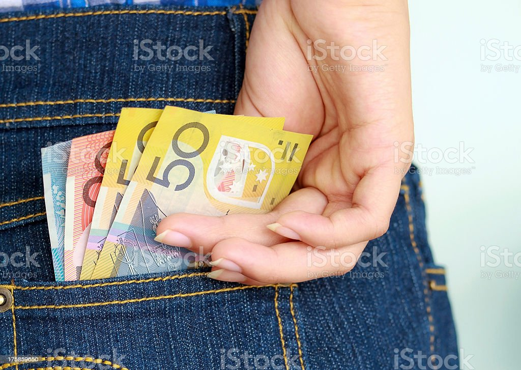 Closeup of hand taking multicolored banknotes out of pocket stock photo