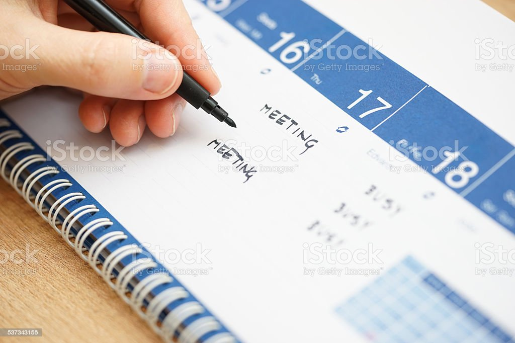 closeup of hand writing events on calendar stock photo