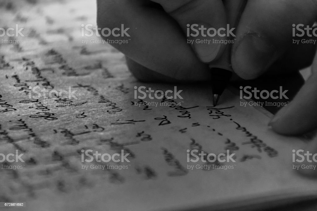 Close-Up Of Hand Writing On Paper stock photo