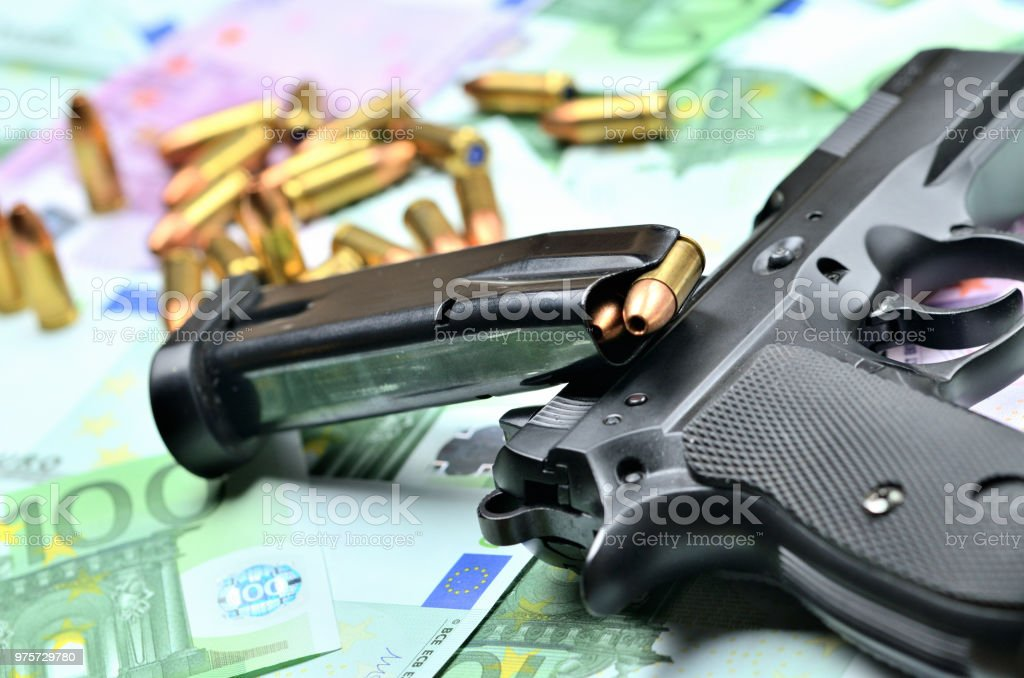 Close-up of handgun, loaded magazine and bullets on euro banknotes background stock photo