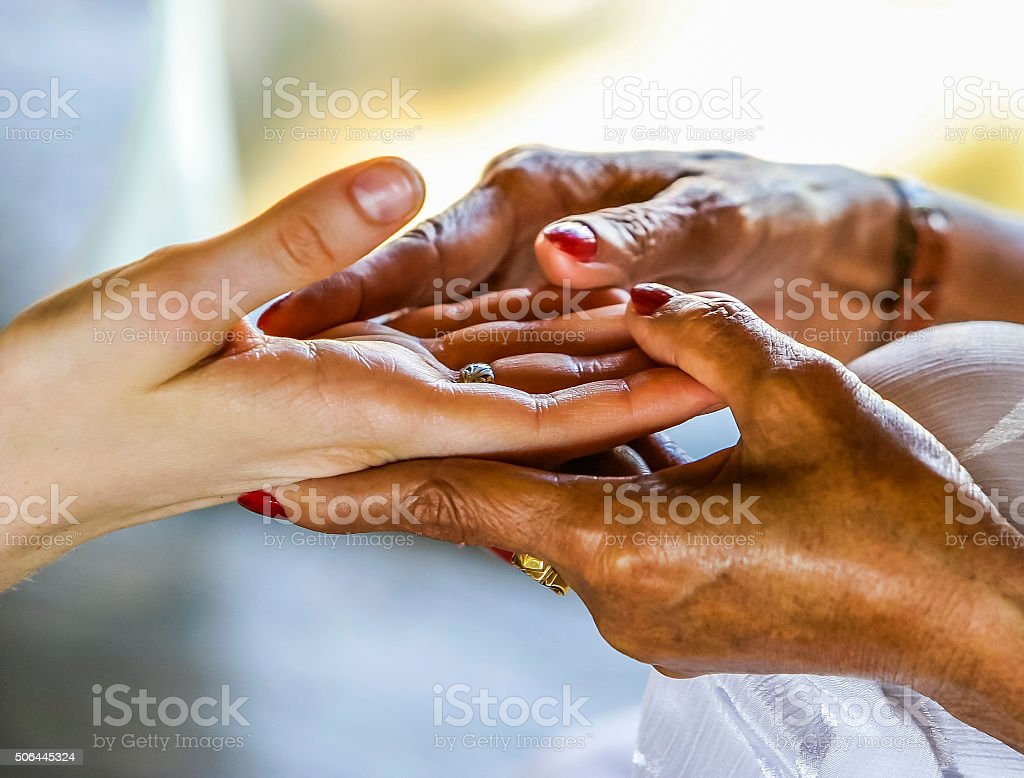 Close-up of hands as older woman reads palm stock photo