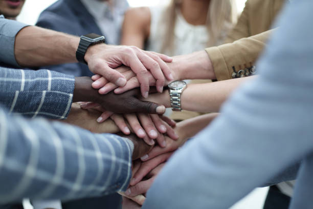 close-up of hands business team showing unity with putting their hands together - responsible business stock photos and pictures