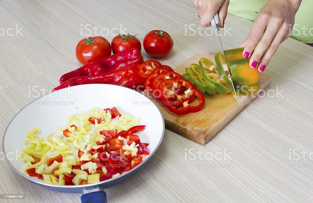 Closeup of hands chopping vegetables in the kitchen royalty-free stock photo