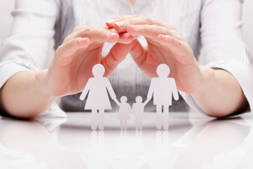 istock Closeup of hands cupping over white paper cutout of a family 166769374