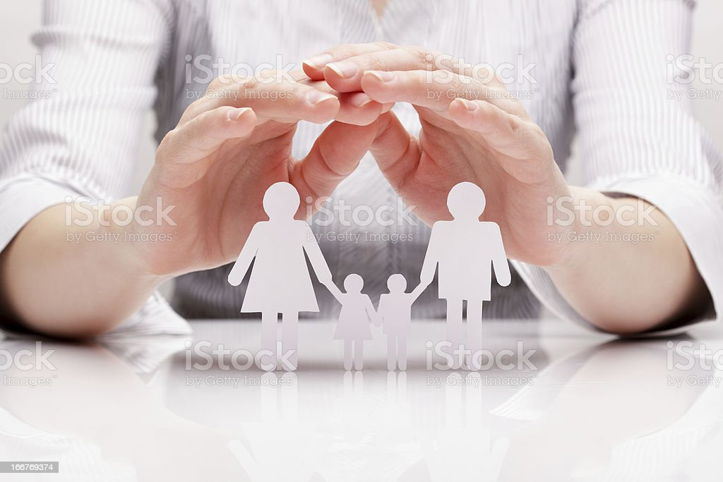 Closeup of hands cupping over white paper cutout of a family stock photo