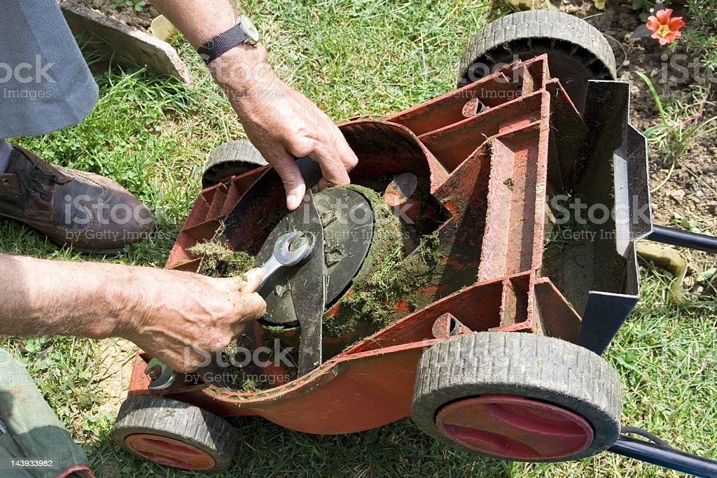 Close-up of hands fixing an overturned lawnmower with wrench stock photo