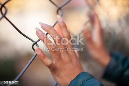 Outdoor close-up image of woman hands holding chain-link fence.