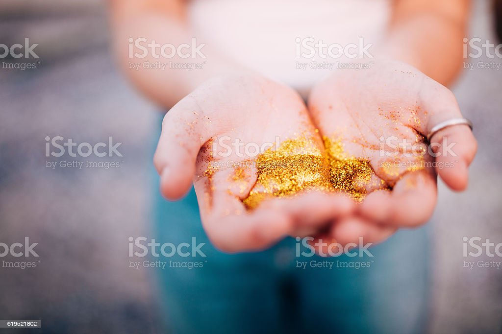 Close-up of Hands holding golden glitter stock photo