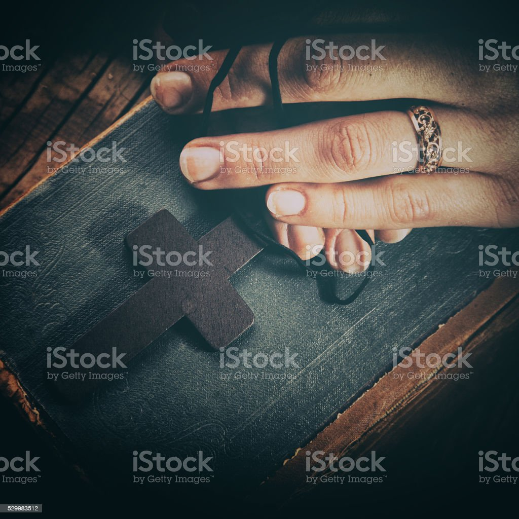 2a74b8c44 closeup of hands holding vintage cross on Bible royalty-free stock photo
