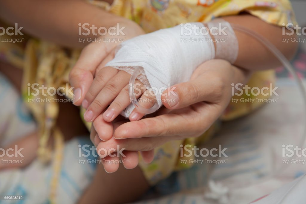 Closeup of hands of a little Boy attaching intravenous tube to patient's hand in hospital bed, And the hands of mother with love. stock photo